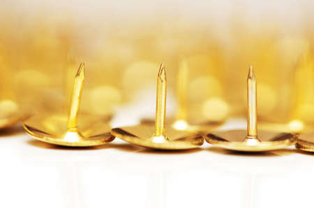 Golden pins isolated on the white background photo