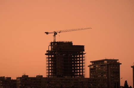 Construction crane building a  skyscraper at sunset photo
