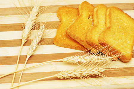 Four toast pieces and wheat ears  on wooden board Stock Photo - 956261