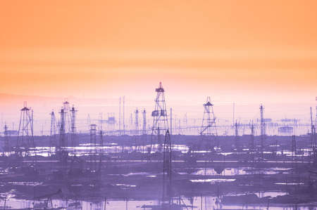 roughneck: Oil derricks on early  morning - Caspian see near Baku