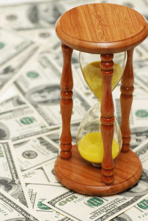path to wealth: Time is money with dollar notes and hourglass Stock Photo