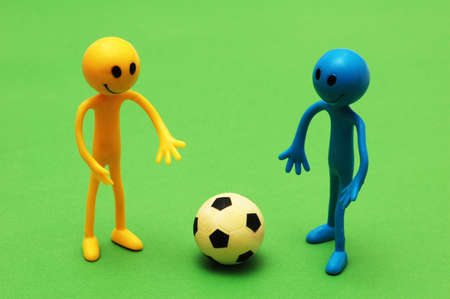 Two smilies playing  football on green pitch photo
