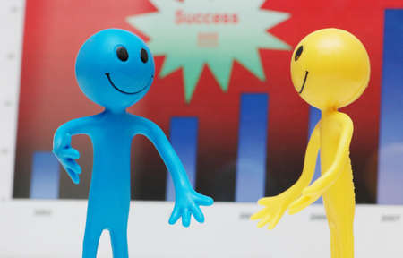 scrutiny: Two smilies discussing business results  over charts