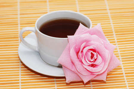 Cup of black tea and rose on  orange mat photo