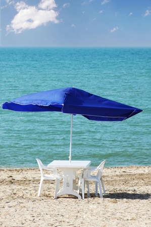 Table, chairs and parasol on  the beach photo