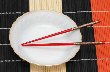 White plate and chopsticks  on wooden mat Stock Photo - 1215628