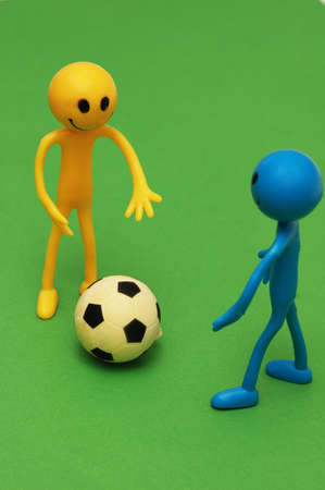tabassum: Two smilies playing  football on green pitch Stock Photo