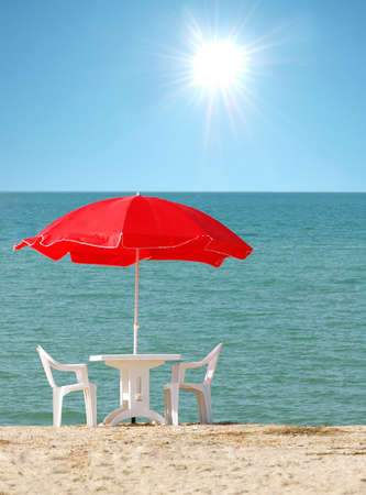 Table with parasol on the beach photo