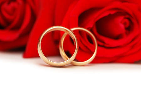 Two wedding rings and red  roses isolated on white photo