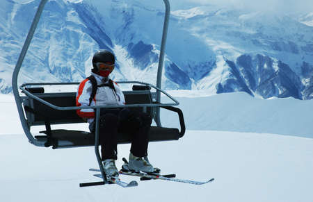 Skier on chair lift at ski resort photo