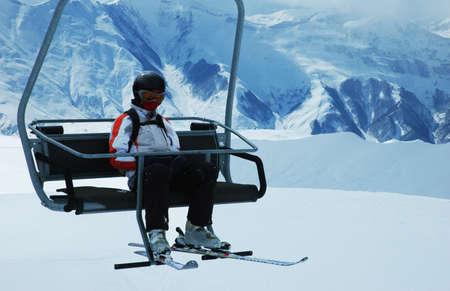 Skier on chair lift at ski resort photo