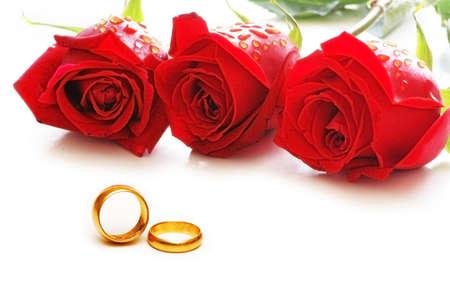 anillos de boda: Tres rosas y anillos aislados en el blanco