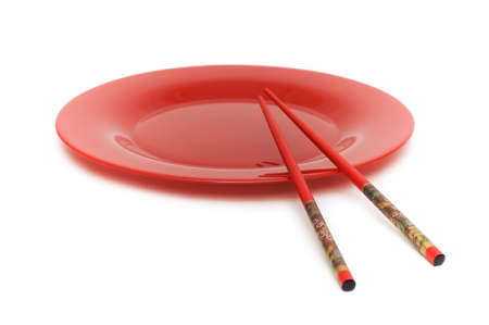 Red plate and chopsticks isolated on the white photo