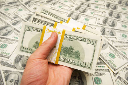 Hand holding american dollars against money background photo