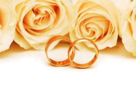 anniversario matrimonio: Rose e anelli di nozze isolato sul bianco