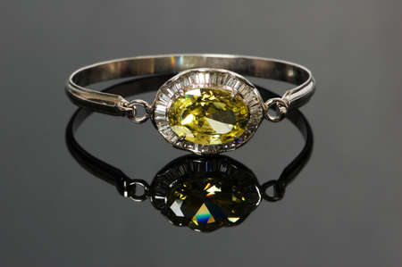Bracelet with yellow stone on reflective background photo