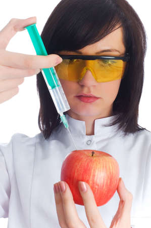 Woman scientiest injecting chemicals into apple on white Stock Photo - 3116374