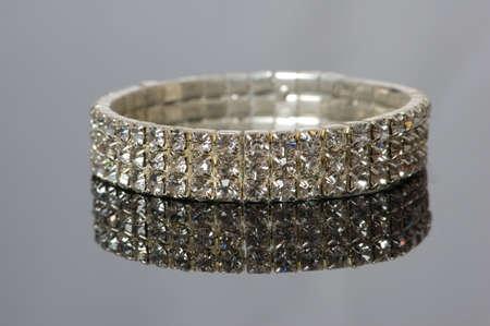 Diamond bracelet with many stones on reflective background photo
