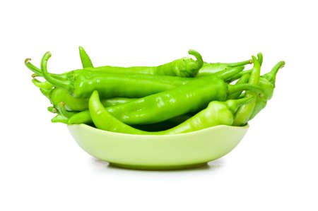 Green peppers in the plate isolated on white photo