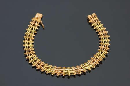 Close up of golden necklace on black shiny background photo