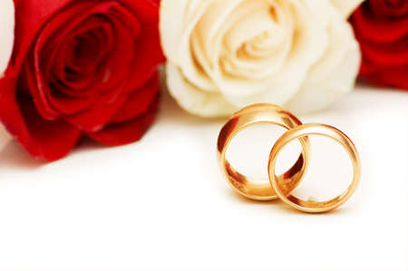 Golden rings and roses isolated on the white photo