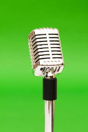 Vintage microphone against the bright green background photo