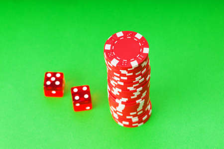 Casino chips and dice against green background Stock Photo - 4655278