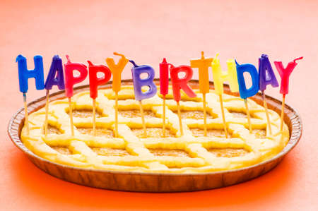 Happy birthday candles in the pie Stock Photo