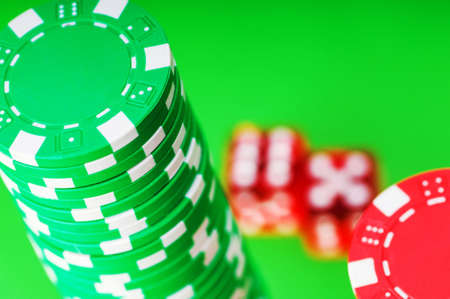 Casino chips and dice against green background photo