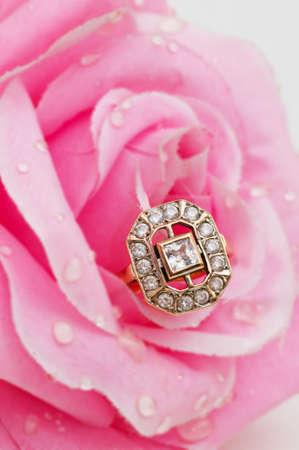 Golden ring against pink rose photo