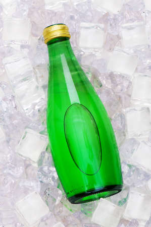 Green bottle of water on ice cubes photo