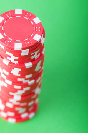 Stack of red casino chips against green background photo