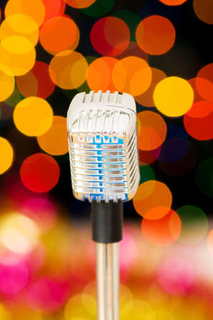 Vintage microphone against blurred lights photo