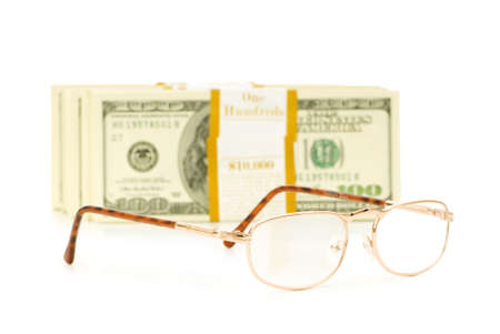Glasses and dollar stack isolated on white photo