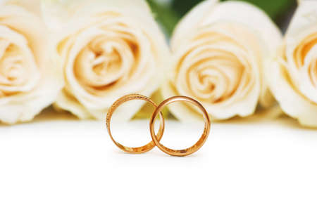 Roses and wedding rings isolated on the white photo