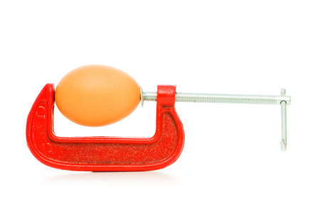 Strength concept with egg and clamp on white Stock Photo - 6373706
