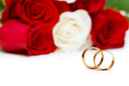 Wedding concept with roses and golden rings photo