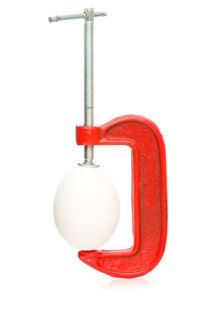 Strength concept with egg and clamp on white photo