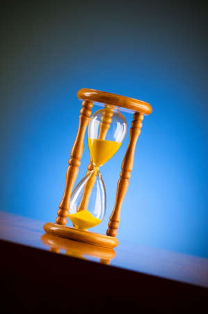 Time concept with hourglass against background Stock Photo - 6553640