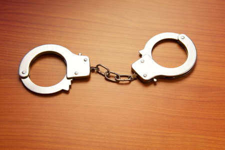 Metal handcuffs on the wooden background Stock Photo - 7045840