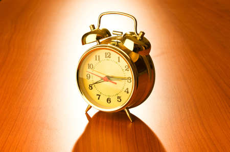 Alarm clock against wooden background photo
