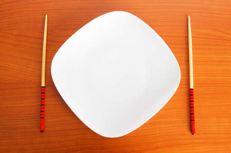chopstick: Plate with chopsticks on the wooden table Stock Photo
