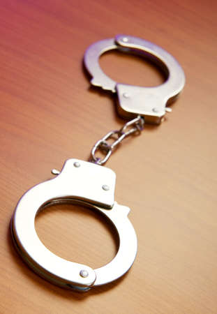 Metal handcuffs on the wooden background photo