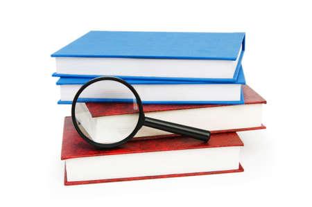 leerboek: Vergroot glas op de stapel boeken  Stockfoto