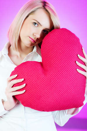 Romantic concept with girl and heart-shaped pillow photo