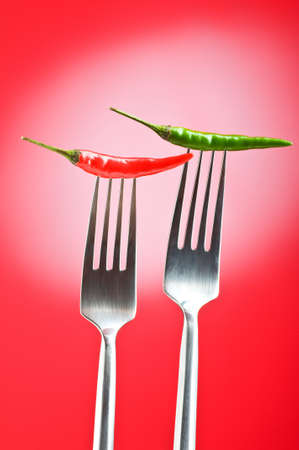 Hot pepper on the fork against colour background photo