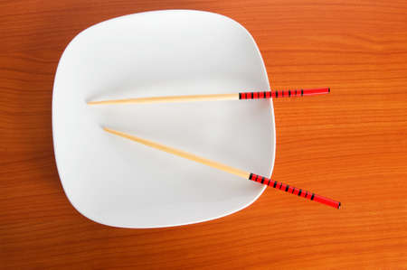 Plate with chopsticks on the wooden table photo