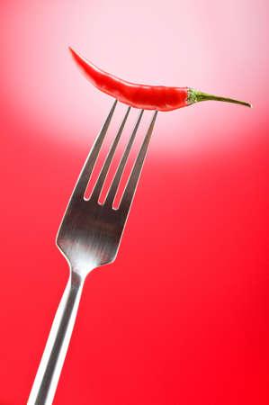 capsaicin: Hot pepper on the fork against colour background