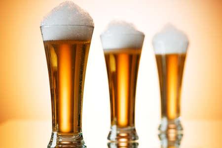 brew beer: Vasos de cerveza contra el fondo degradado multicolor