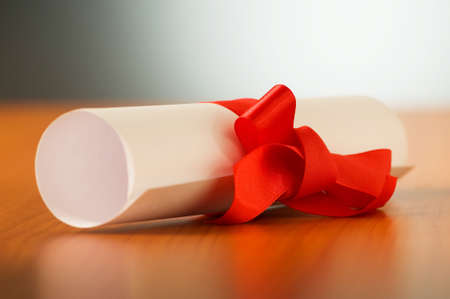 Education concept - diploma roll on the wooden table Stock Photo - 7518345